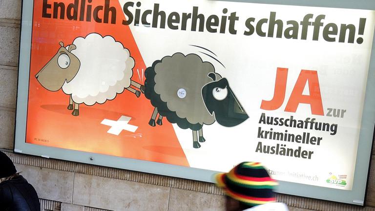 """Ein Mann geht an einem Plakat der Schweizerischen Volkspartei vorbei, auf dem die """"Ausschaffung"""" (Ausweisung) krimineller Ausländer gefordert wird; Foto: dpa"""