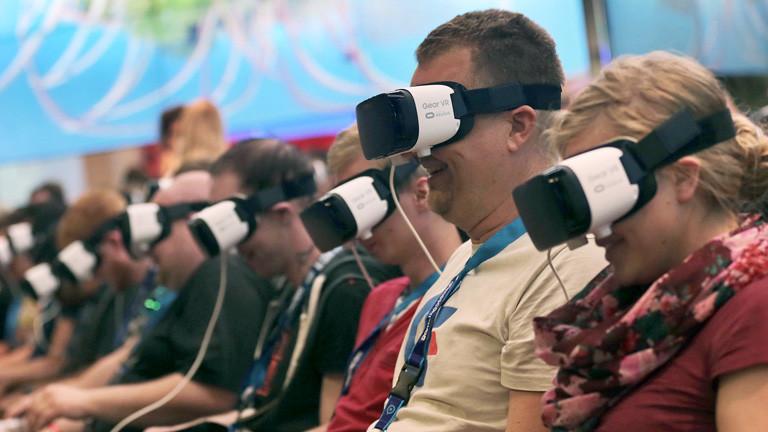Fachbesucher sitzen auf der Gamescom 2016 mit der Virtual Reality-Brillen nebeneinander. Sie erleben eine vierdimensionale Achterbahnfahrt; Foto: dpa
