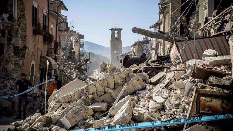 Nach dem schweren Erdbeben (24.08.16) sind Häuser entlang einer schmalen Straße in dem Ort Amatrice zerstört. Am Ende der Straße steht noch ein Kirchturm.