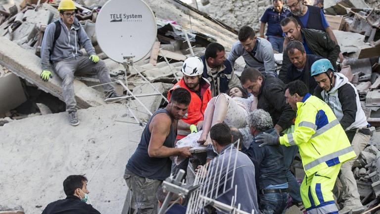 Nach dem schweren Erdbeben in Italien (24.08.16) wird eine junge Frau auf einer Trage von Männern aus einem Haus gerettet; Foto: dpa