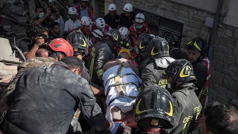 Helfer retten eine Person auf einer Trage nach dem Erdbeben in Italien (24.08.16) .