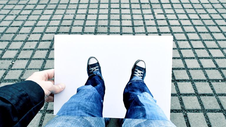 Auf einem Ausdruck sind Füße zu sehen. Eine Hand hält den Ausdruck an seine Beine.