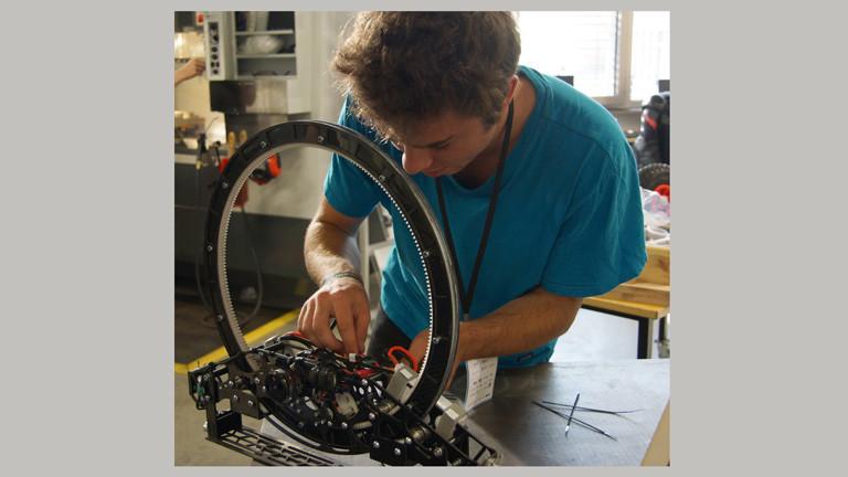 Maximilian Reif beugt sich über den Roboter für den Weltraumlift. Er fixiert Kabel.