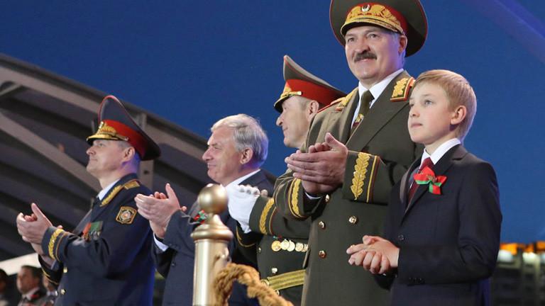 Alexander Lukaschenko bei einer Militärparade (04.07.2014). Neben ihm steht sein Sohn; Foto: dpa