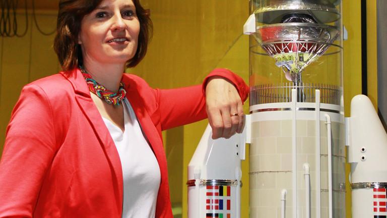 Tina Büchner da Costa lehnt sich gegen eine nachgebaute Weltraumrakete.