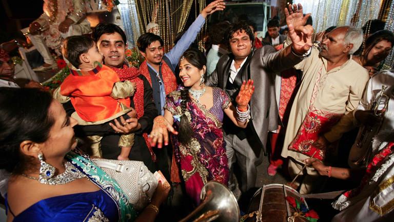 Auf einer indischen Hochzeit tanzen die Gäste.