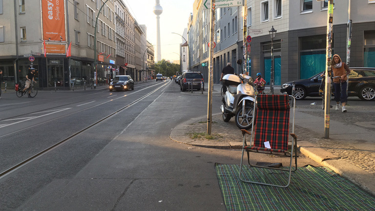 Auf einem Parkplatz mitten in Berlin liegt eine Decke. Darauf steht ein Liegestuhl.