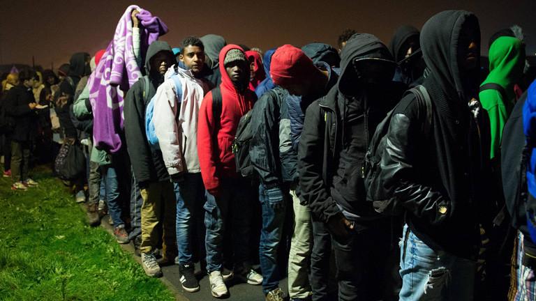 Flüchtlinge stehen in einer langen Schlange.