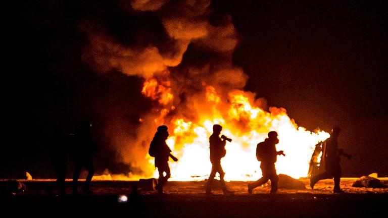 Bei der Räumung des Lagers in Calais. In der Nacht gehen Polizisten vor Feuern entlang.