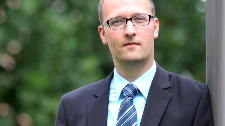 Florian Endres (19.09.2014) von der Beratungsstelle Radikalisierung des BAMF. Er hat kurze Haare. Er trägt Brille, Anzug und Schlips; Foto: dpa, Robert Ullinger/BAMF