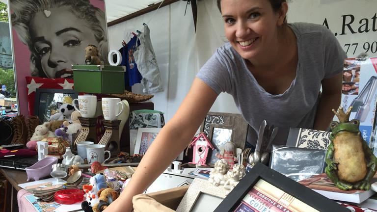 Marlene Mohn steht hinter ihrem Flomarktstand. Sie verkauft Gegenstände, die sie ausgemistet hat.