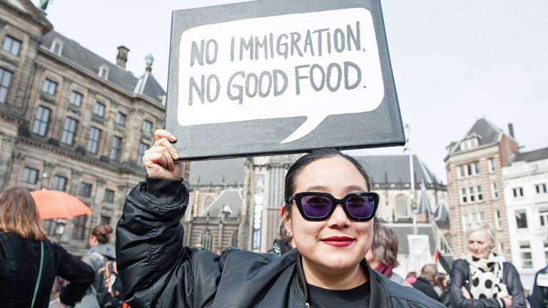 """Bei einer Demonstration für Frauenrechte am 11. März 2017 hält in Amsterdam eine Frau ein Schild in die Luft, darauf steht """"no immigration, no good food""""."""