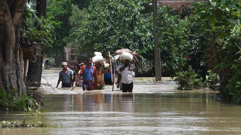 Nach schweren Regenfällen sind Regionen im indischen Bundesstaat Bihar unter Wasser. Menschen laufen durch Wasser und tragen Säcke auf den Köpfen.