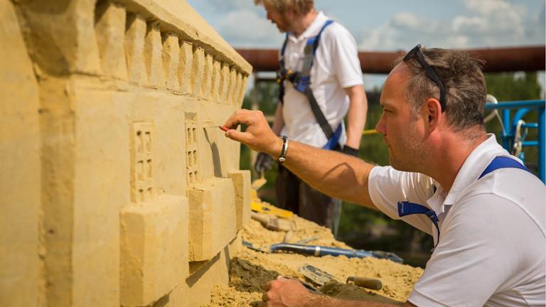 Ein Mann arbeitet an der fast fertigen Sandburg. Er arbeitet kleine Fenster in den Sand.
