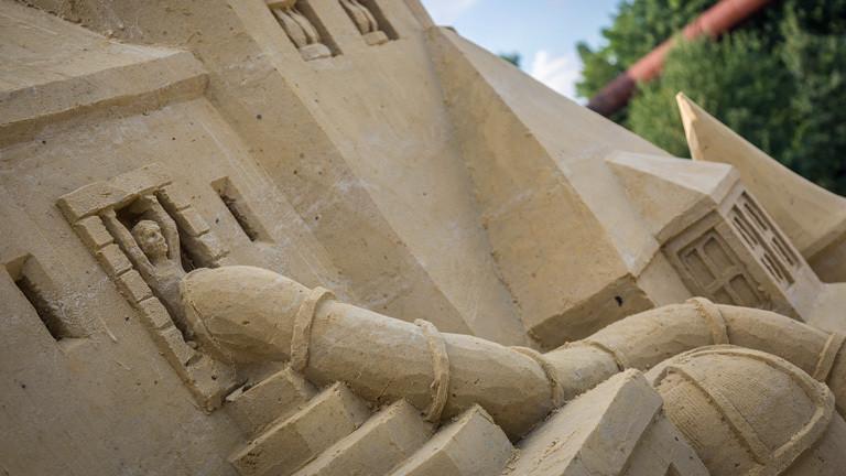 Details der fast fertigen Sandburg. In den Sand ist eine Person gearbeitet, die in eine Röhrenrutsche steigt.