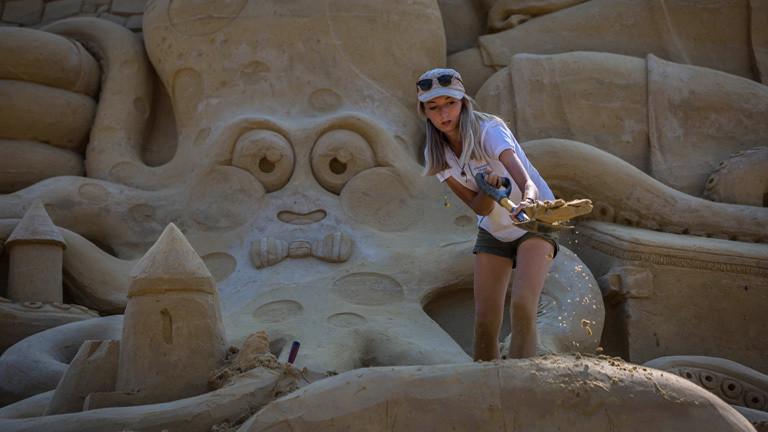Eine Frau schaufelt Sand weg. Sie steht vor der fast fertigen 15 Meter hohen Sandburg. Hinter ihr ist unter anderem ein Krake in den Sand gearbeitet.
