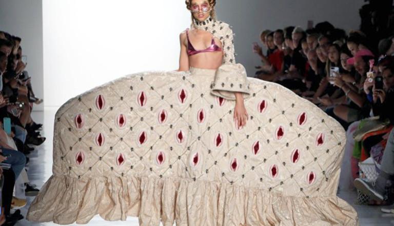 Ein Model trägt ein weißes Kleid mit weitem Rock, das mit Vulva-Applikationen verziert ist.
