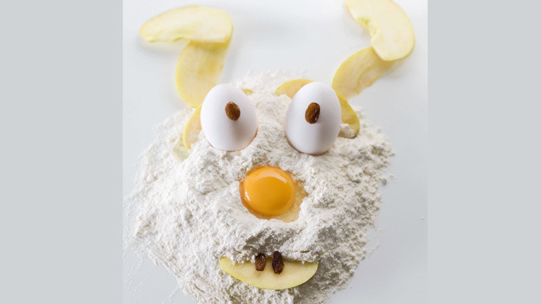 Auf einem Haufen Mehl liegt ein Eigelb, das wie eine Nase wirkt. Darüber stecken zwei Eier mit Rosinen, die an Augen erinnern.
