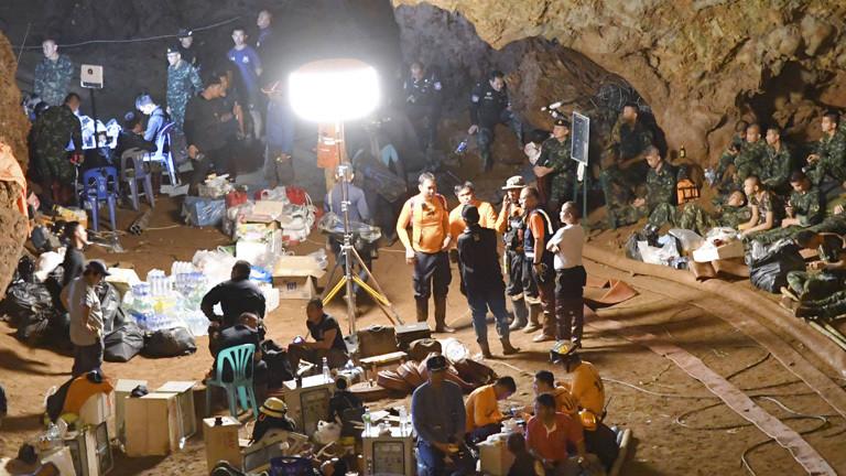 In einer Höhe sind Rettungskräfte versammelt mit ihrer Ausrüstung. Sie sollen die Jungen plus Trainer aus de Höhle retten.