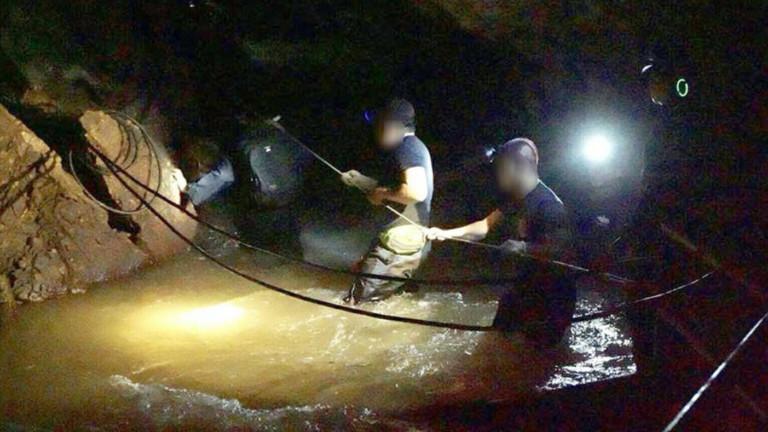 Rettungskräfte auf dem Weg zur Höhle, in denen ein Fußballteam und der Trainer gefangen sind. Die Retter stapfen durch tiefes Wasser.