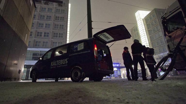 Auf dem Alexanderplatz in Berlin steht ein Kleinbus. Die hintere Klappe ist offen. Auf dem Bus steht seitlich Kältebus.