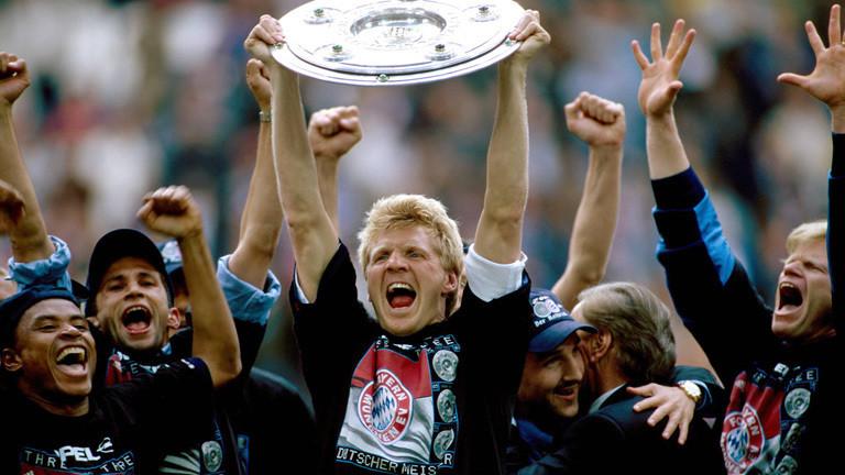 Nachdem Bayern München 2001 die Meisterschaft gewonnen hat. Steht der Fußballer Stefan Effenberg zwischen Teiler des Teams und streckt die Meisterschale in die Luft.