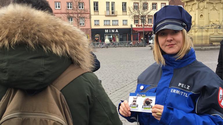 Pelzermittlerinnen Simone Sommerfeld spricht mit einem Passanten, an dessen Jacke ist ein Pelzkragen angebracht.