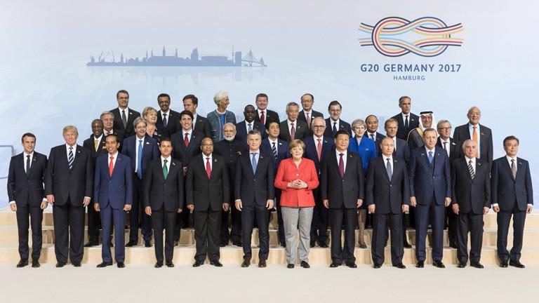 Gemeinsames Foto der Teilnehmer des G20-Gipfels in Hamburg 2017. Merkel trägt einen roten Blazer und eine beige Hose. Die Kleidung der anderen Gipfel-Teilnehmer ist schwarz oder blau.