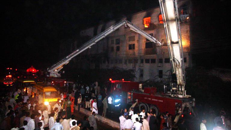 Am 11.09.2012 brennt eine Textilfabrik im pakistanischen Karatschi. Feuerwehrfahrzeuge stehen vor dem Gebäude. Rettungskräne sind ausgefahren. Hinter den Fenstern sieht man die Flammen.. Bei dem Brand starben 250 Menschen.