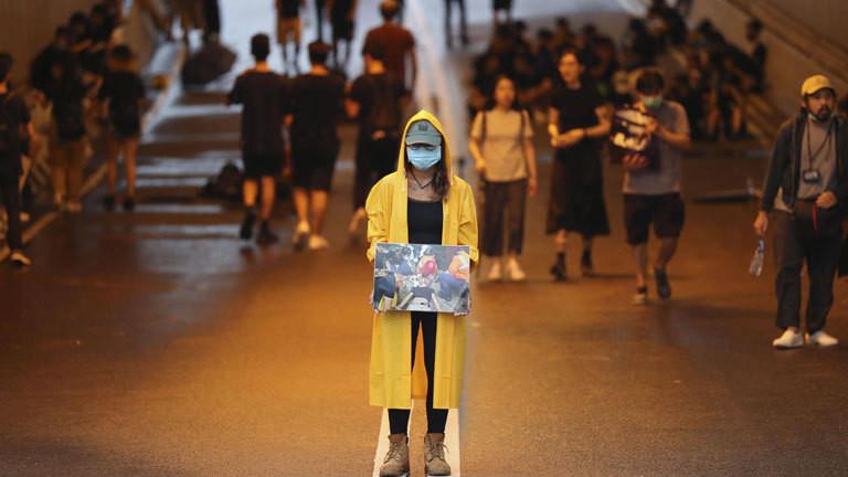 In Hongkong demonstrieren Menschen gegen ein geplantes Auslieferungsgesetz. Eine Frau mit gelbem Regenmantel hält ein Foto, darauf  ist ein verletzter Mensch abgebildet.