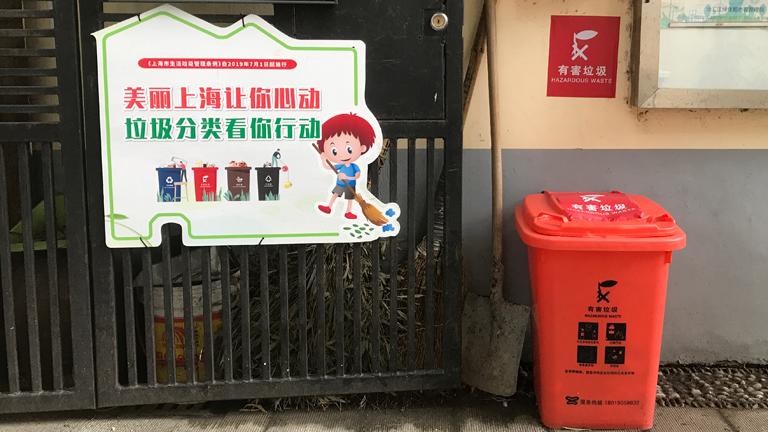 Eine rote Mülltonne, darüber ein Schild, auf dem Hazard steht, links davon ein Werbeschild für das Mülltrennungssystem