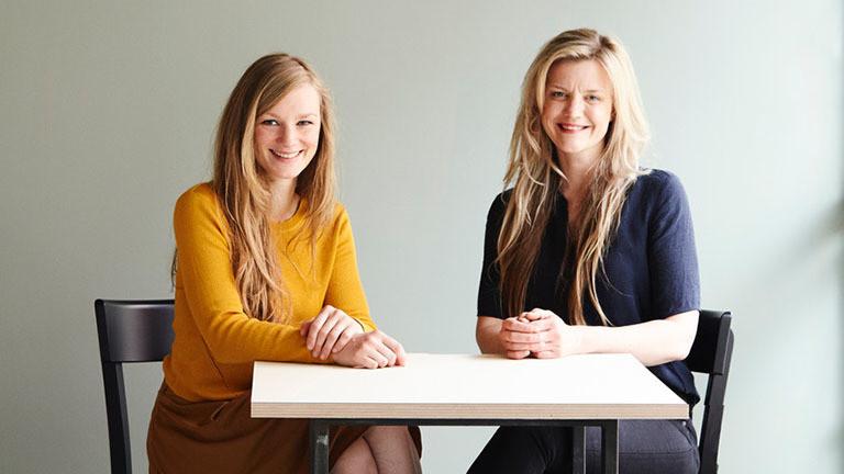 Die Restaurantbetreiberinnen Iga Raczka (rechts) und Julia Wallstab sitzen nebeneinander an einem Tisch.