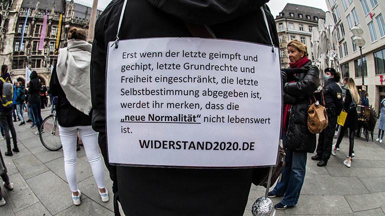 Bei einem Protest in München trägt jemand ein Schild mit sich, darauf ist ein Hinweis auf Widerstand2020 (02.05.2020)