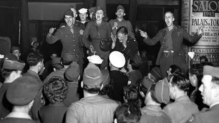 Schwarz-Weiß-Foto: Französische und US-amerikanische Soldaten - auch angehörige des Women's Army Corps - feiern auf den Grands Boulevards in Paris die deutsche Kapitulation am 8. Mai 1945.