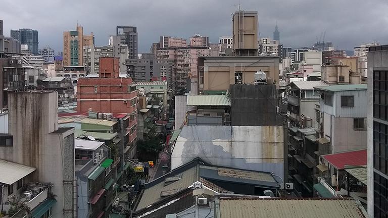 Blick aus dem Hotelzimmer auf Taipeh; viele Häuser unterschiedlicher Höhe reihen sich aneinander.