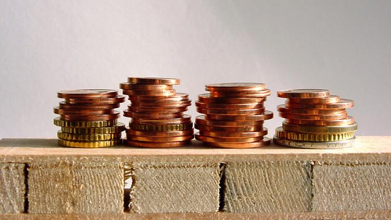 Einige Münzen liegen aufgestapelt auf einer Europalette.