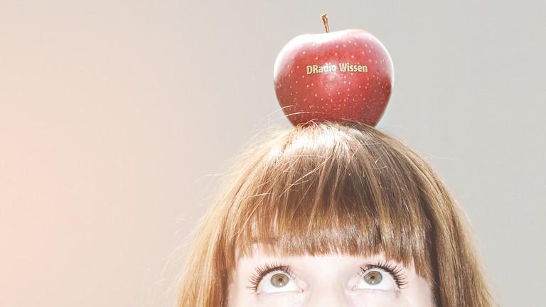 """Marlis Schaum mit einem Apfel auf dem Kopf, auf dem """"DRadio Wissen"""" steht"""