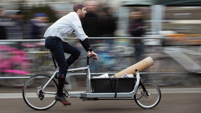 Ein Fahrradfahrer transportiert Lasten mit einem Lastenfahrrad