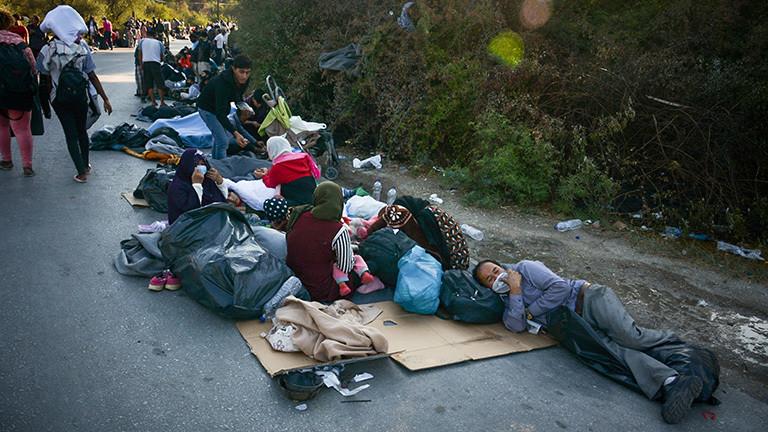Auf einer Landstraße auf der griechischen Insel Lesbos ruhen sich Flüchtlinge aus, die sich aus dem brennenden Lager Moria gerettet haben (09.09.2020)