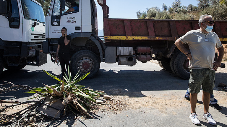Auf der Insel Lesbos haben Bewohner eine Straßenblockade errichtet; zwei Lkw stehen quer auf der Straße; ein Mann mit Mundschutz steht davor (10.09.2020)
