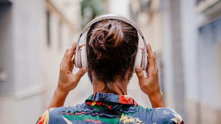 Ein Mann geht eine Straße entlang und trägt Kopfhörer. Er ist nur von hinten zu sehen, sein Kopf und seine Schultern.