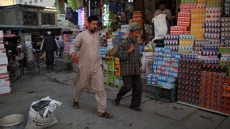 Straßenszene in Kabul; zwei Männer laufen auf einem Markt vor einem Stand mit vielen Glühbirnen (15.9.2021)