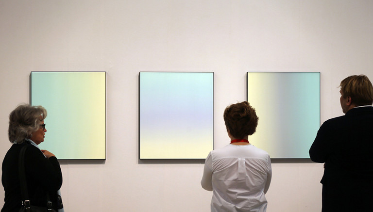 Galeristen und Besucher schauen sich am 09.04.2014 in Köln (Nordrhein-Westfalen) auf der Kunstmesse Art Cologne (10.-13.04.2014) auf dem Stand der Galerie Esther Schipper Bilder von Matti Braun an.