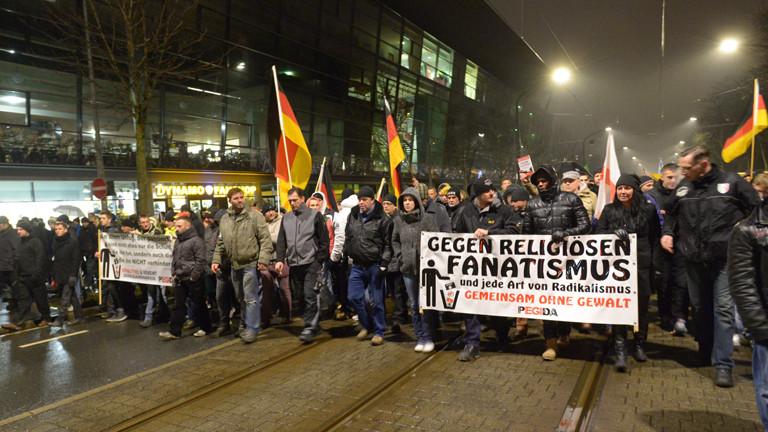 Teilnehmer der islamkritischen Pegida-Bewegung ziehen am 05.01.2015 mit Transparenten und Fahnen bei einer Kundgebung in Dresden (Sachsen) am Stadion des Fußball-Drittligisten Dynamo Dresden vorbei.
