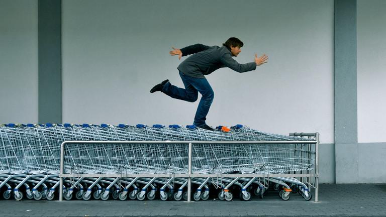 Ein Mann steht auf Einkaufswagen.