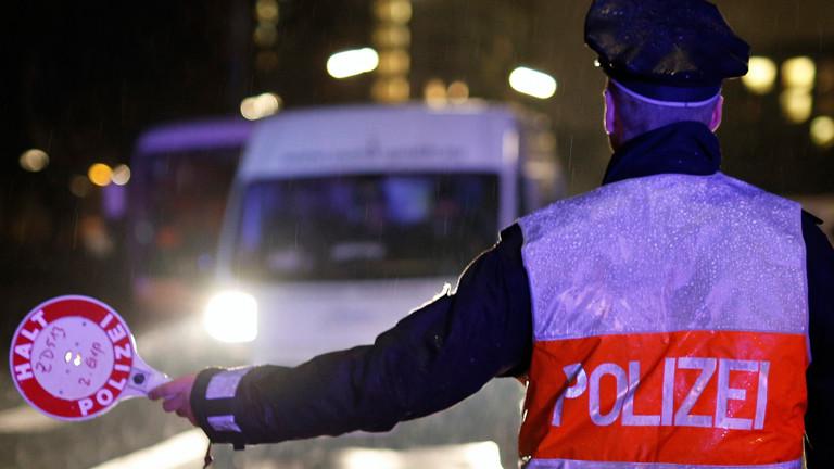 Ein Polizeibeamter hält am 20.02.2015 in Hamburg ein Fahrzeug zu einer Verkehrskontrolle an.