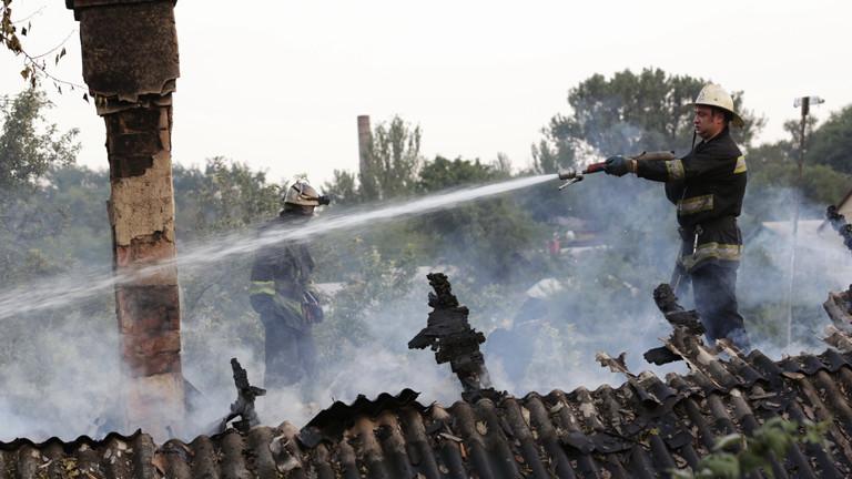 Feuerwehrmänner löschen in Donezk einen Hausbrand nach Artillerie-Beschuss (14.08.2014 / dpa).