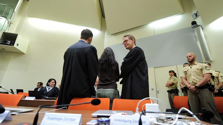 Die Angeklagte Beate Zschäpe steht zwischen ihren Anwälten Wolfgang Stahl und Wolfgang Heer im Gerichtssaal in München.