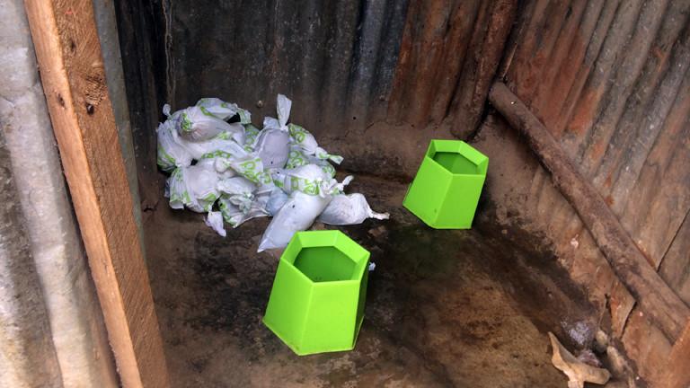 Die Plastikeimer und Peepoople Tüten in einem begehbaren Container