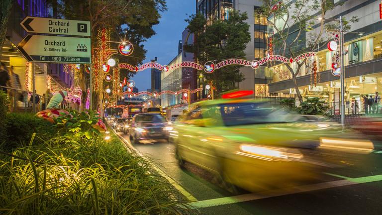 Gelbes Taxis fährt nachts durch Singapur